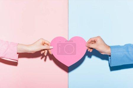 Photo pour Vue recadrée de l'homme et de la femme tenant une carte en forme de coeur sur fond rose et bleu - image libre de droit