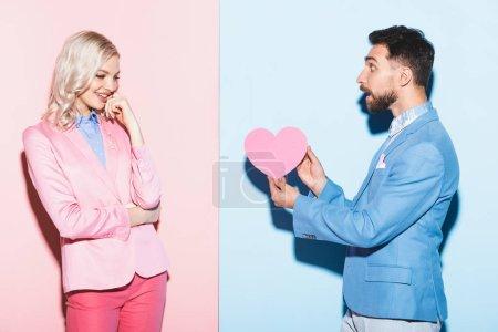 Photo pour Homme choqué donnant carte en forme de coeur à la femme souriante sur fond rose et bleu - image libre de droit