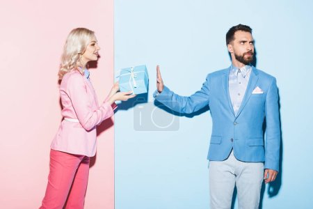 smiling woman giving gift to offended man on pink and blue background