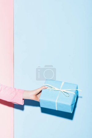 cropped view of woman holding gift box on pink and blue background
