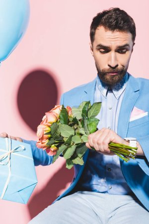 Photo for Handsome and nervous man looking at wristwatch and holding balloon, gift and on bouquet blue and pink background - Royalty Free Image
