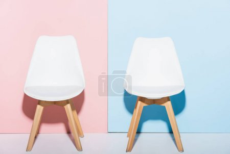 Photo for Wooden and white chairs on pink and blue background - Royalty Free Image