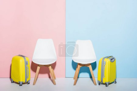 Photo for Wooden chairs and travel bags on pink and blue background - Royalty Free Image
