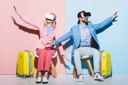Photo for Woman and smiling man in virtual reality headsets with outstretched hands on pink and blue background - Royalty Free Image