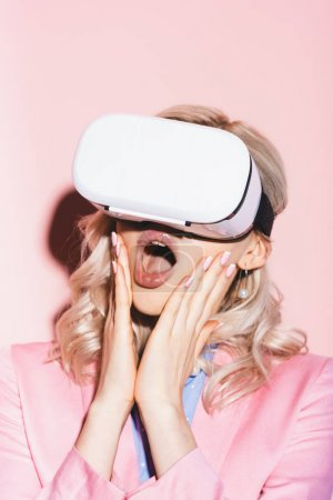 schockierte Frau in Virtual-Reality-Headsets auf rosa Hintergrund