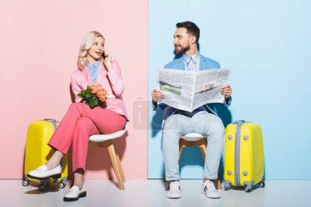 attraktive Frau im Smartphone-Gespräch und lächelnder Mann mit Zeitung auf rosa und blauem Hintergrund