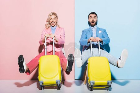 Photo for Shocked woman and handsome man holding travel bags on pink and blue background - Royalty Free Image