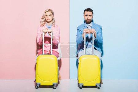 Foto de Mujer triste y hombre guapo sosteniendo bolsas de viaje sobre fondo rosa y azul - Imagen libre de derechos