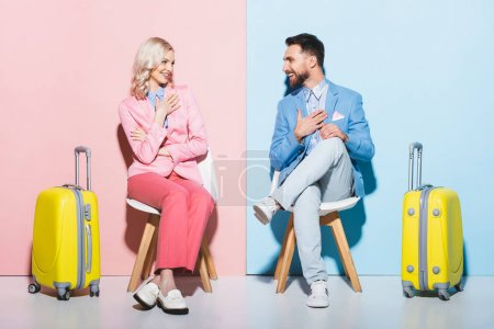 smiling woman and handsome man looking at each other on pink and blue background