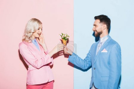 smiling man giving bouquet to shocked woman on pink and blue background