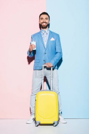 Photo for Smiling man with cocktail holding travel bag on pink and blue background - Royalty Free Image