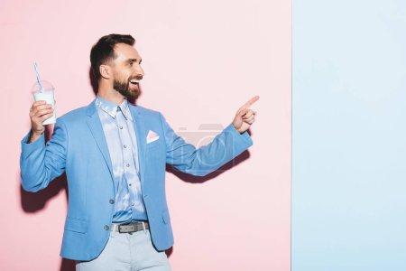 lächelnder Mann mit Cocktail und Zeigefinger auf rosa und blauem Hintergrund