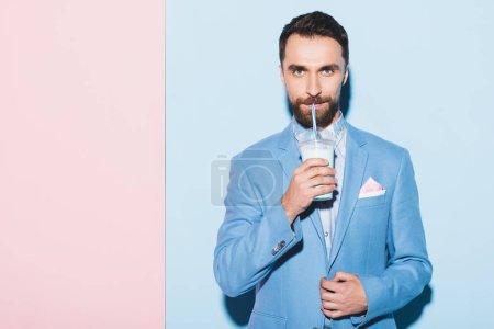 Photo pour Bel homme qui boit un cocktail sur fond rose et bleu - image libre de droit