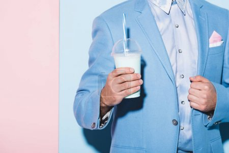 abgeschnittene Ansicht eines Mannes mit Cocktail auf rosa und blauem Hintergrund