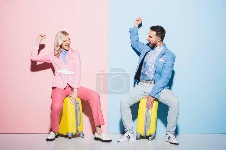Photo pour Femme souriante et bel homme assis sur des sacs de voyage et montrant un geste oui sur fond rose et bleu - image libre de droit