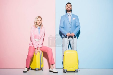 smiling woman and handsome man sitting on travel bags on pink and blue background