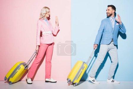 uśmiechnięta kobieta i przystojny mężczyzna z torbami podróżnymi machając na różowym i niebieskim tle