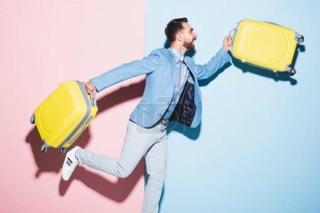Photo pour Homme souriant tenant des sacs de voyage sur fond rose et bleu - image libre de droit