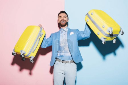 smiling man holding travel bags on pink and blue background