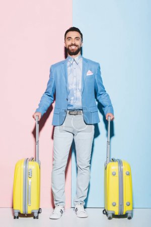 Photo for Smiling man holding travel bags on pink and blue background - Royalty Free Image