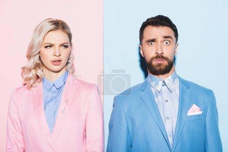 irritierte Frau und schöner Mann auf rosa und blauem Hintergrund