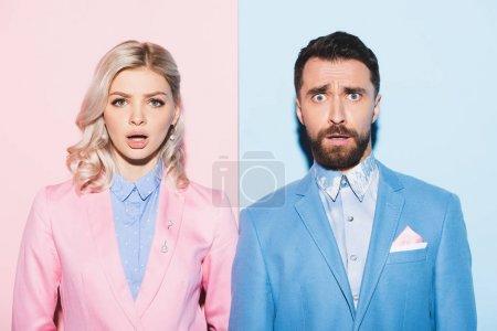schockierte Frau und gutaussehender Mann blicken in die Kamera auf rosa und blauem Hintergrund