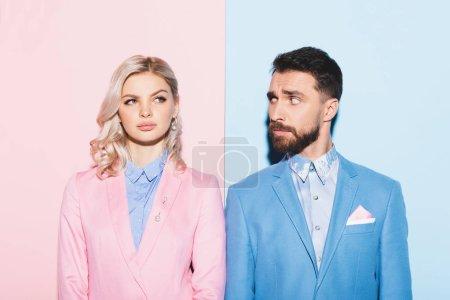 verträumte Frau und schöner Mann, der sie auf rosa und blauem Hintergrund ansieht