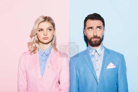 Photo pour Femme rêveuse et beau regard loin homme sur fond rose et bleu - image libre de droit