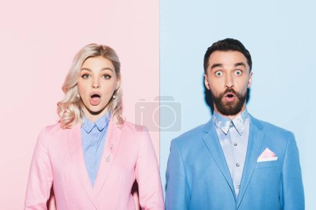 Photo for Shocked woman and handsome man looking at camera on pink and blue background - Royalty Free Image