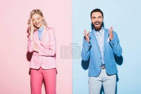 Photo pour Femme souriante et bel homme sur fond rose et bleu - image libre de droit