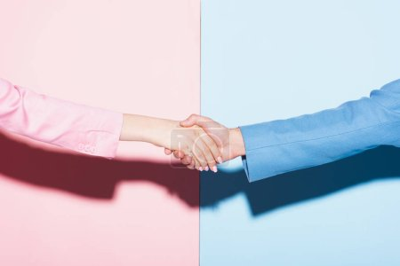 cropped view of woman and man shaking hands on pink and blue background