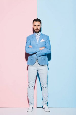 Photo pour Homme sérieux avec les bras croisés regardant caméra sur fond rose et bleu - image libre de droit