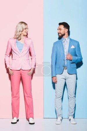 Lächelnde Frau und gutaussehender Mann, die einander auf rosa und blauem Hintergrund anschauen