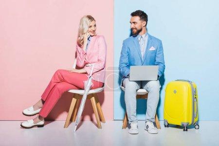 Lächelnde Frau im Smartphone-Gespräch und schöner Mann mit Laptop auf rosa und blauem Hintergrund