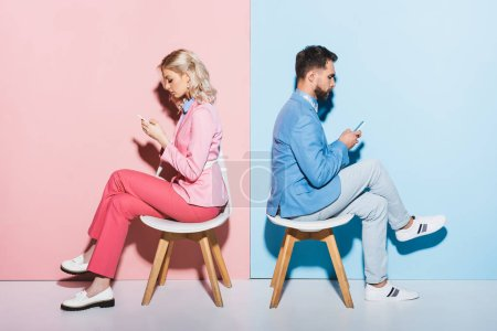 Photo for Side view of woman and handsome man using smartphones on pink and blue background - Royalty Free Image