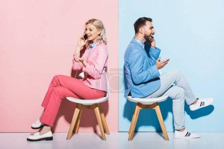 Lächelnde Frau und gutaussehender Mann im Gespräch auf Smartphones auf rosa und blauem Hintergrund