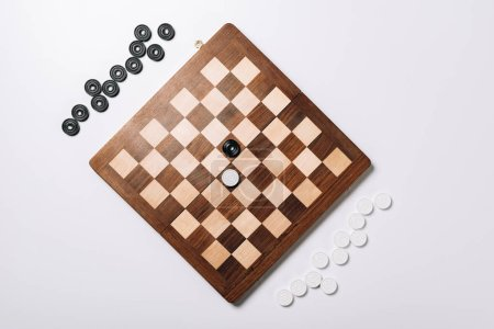 Photo for Top view of checkers on wooden chessboard on white background - Royalty Free Image