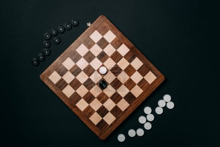Photo for Top view of checkers on wooden chessboard isolated on black - Royalty Free Image