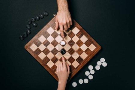 Photo pour Vue du dessus de l'homme et de la femme jouant dames isolées sur noir - image libre de droit