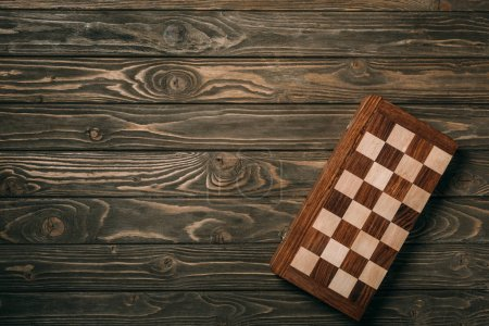 Top view of checkerboard on textured wooden background
