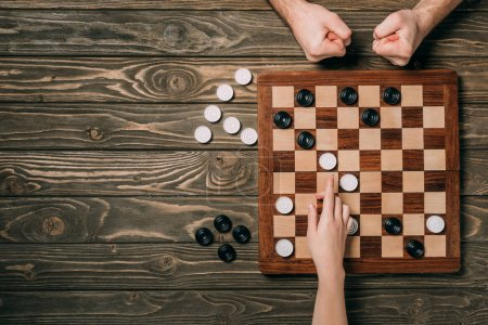 Photo for Cropped view of man and woman playing in checkers on wooden background - Royalty Free Image