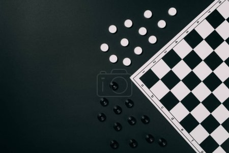 Photo for Top view of black and white checkers and checkerboard isolated on black - Royalty Free Image