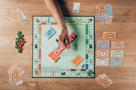 KYIV, UKRAINE - NOVEMBER 15, 2019: Cropped view of man holding dices with monopoly game on table
