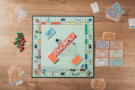 KYIV, UKRAINE - NOVEMBER 15, 2019: Top view of monopoly game with toy currency on wooden table