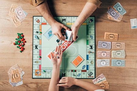 KYIV, UKRAINE - NOVEMBER 15, 2019: Cropped view of woman holding dices and man with explanation cards by monopoly game at table