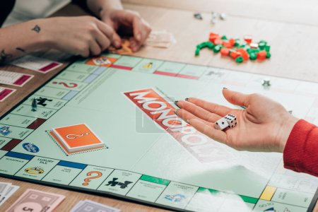 KYIV, UKRAINE - NOVEMBER 15, 2019: Cropped view of woman playing monopoly game at table