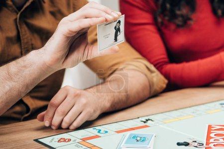 Photo pour KYIV, UKRAINE - 15 NOVEMBRE 2019 : Vue recadrée de l'homme tenant une carte d'explication par une femme avec un jeu monopolistique sur la table - image libre de droit