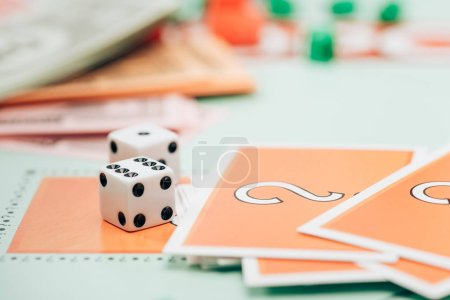 KYIV, UKRAINE - NOVEMBER 15, 2019: Selective focus of dices and cards on monopoly game