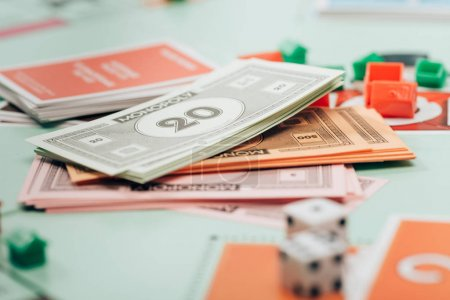 KYIV, UKRAINE - NOVEMBER 15, 2019: Selective focus of toy currency, figures and dices on monopoly game