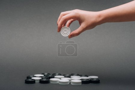 Photo for Cropped view of woman holding white checker isolated on grey - Royalty Free Image